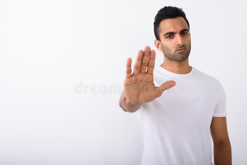 Young handsome Indian man against white background royalty free stock photo