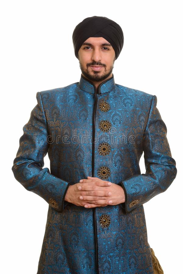 Young handsome Indian Sikh intertwining fingers together wearing royalty free stock photography