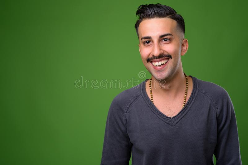 Young handsome Iranian man with mustache against green backgroun. Studio shot of young handsome Iranian man with mustache wearing gray long sleeved shirt against royalty free stock image