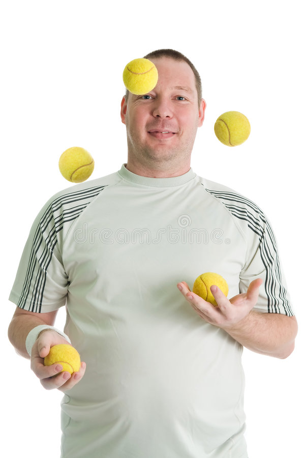 Young handsome juggler. Young man juggling with tennis balls. Isolated over white royalty free stock photography