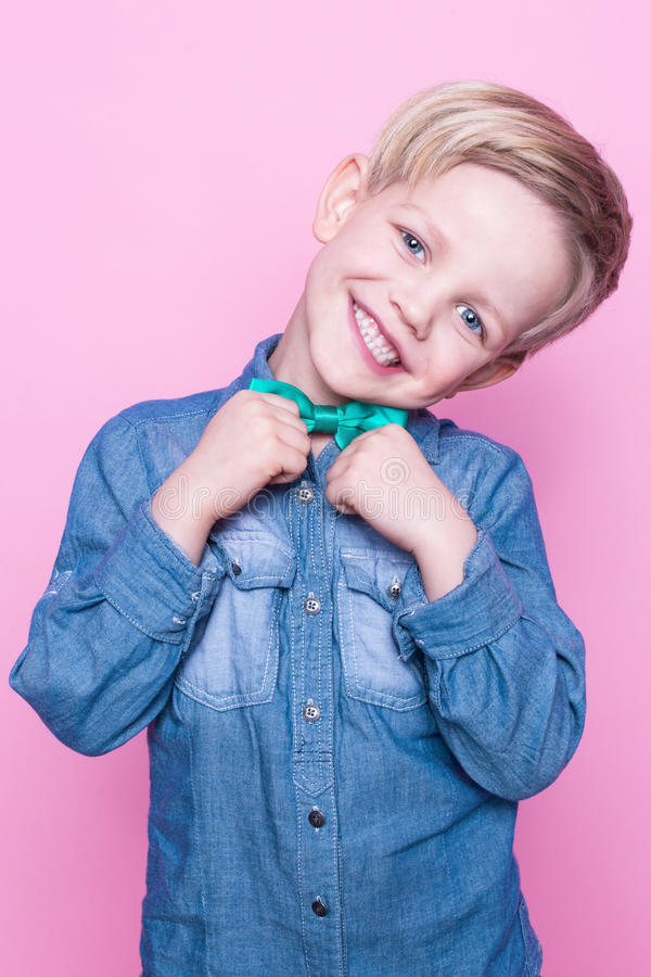 Young handsome kid smiling with blue shirt and butterfly tie. Studio portrait over pink background royalty free stock photography