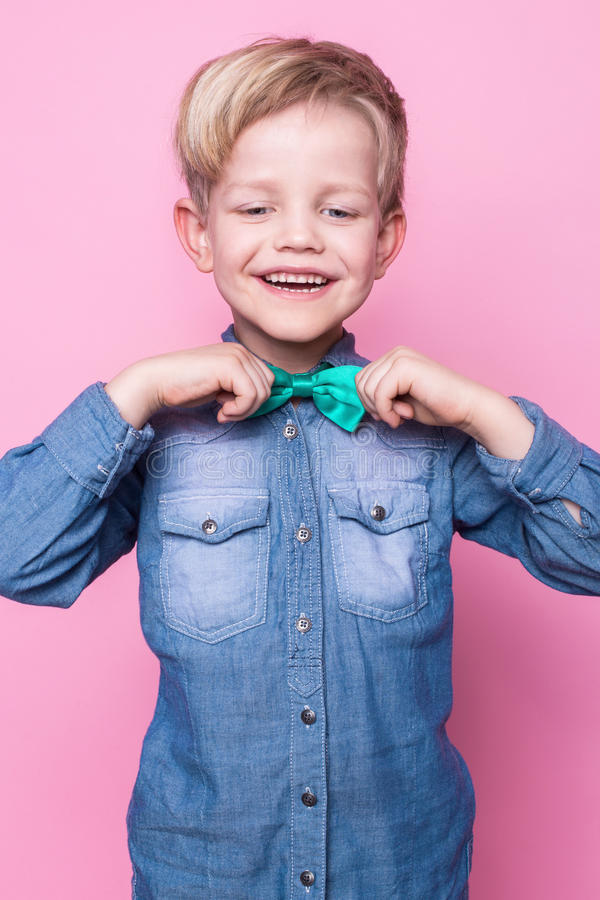 Young handsome kid smiling with blue shirt and butterfly tie. Studio portrait over pink background stock image