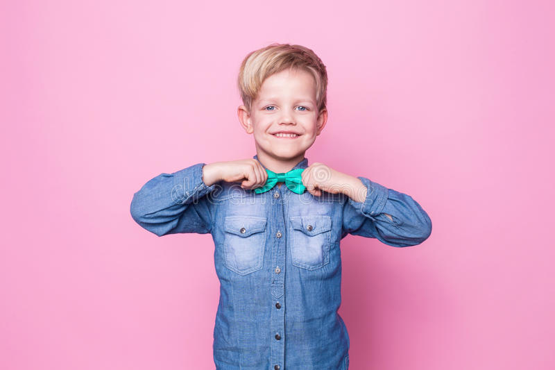 Young handsome kid smiling with blue shirt and butterfly tie. Studio portrait over pink background royalty free stock photos