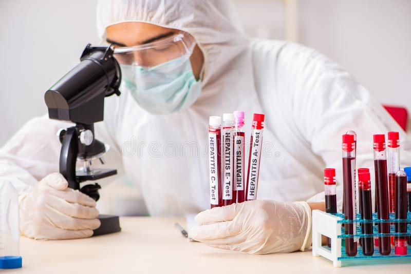 The young handsome lab assistant testing blood samples in hospital. Young handsome lab assistant testing blood samples in hospital stock image