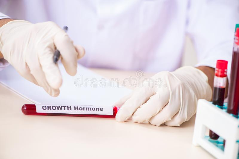 The young handsome lab assistant testing blood samples in hospital. Young handsome lab assistant testing blood samples in hospital royalty free stock photography