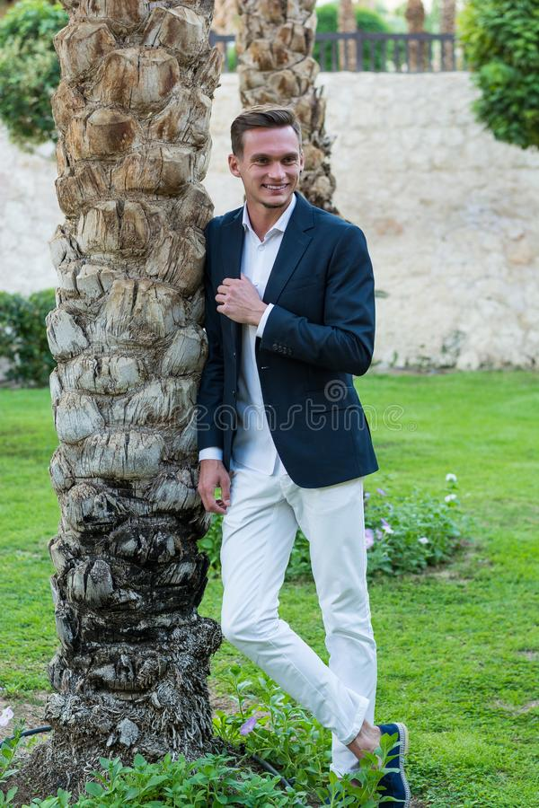 Young handsome laughing man in a white shirt, white trousers and suit stands near the palm tree royalty free stock photos
