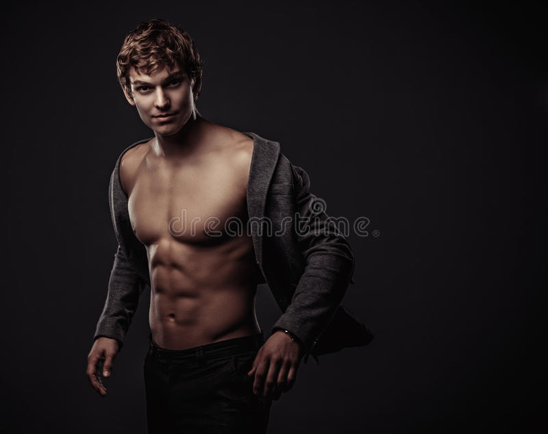 Young handsome macho man with muscle abdominal and open jacket. Fashion studio shoot royalty free stock images