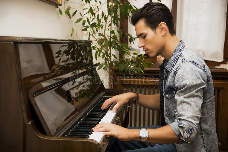 Young handsome male artist playing classical upright piano. Young handsome male artist playing his wooden classical upright piano, indoor portrait royalty free stock images