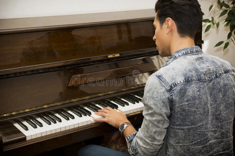 Young handsome male artist playing classical upright piano. Young handsome male artist playing his wooden classical upright piano, indoor portrait stock image