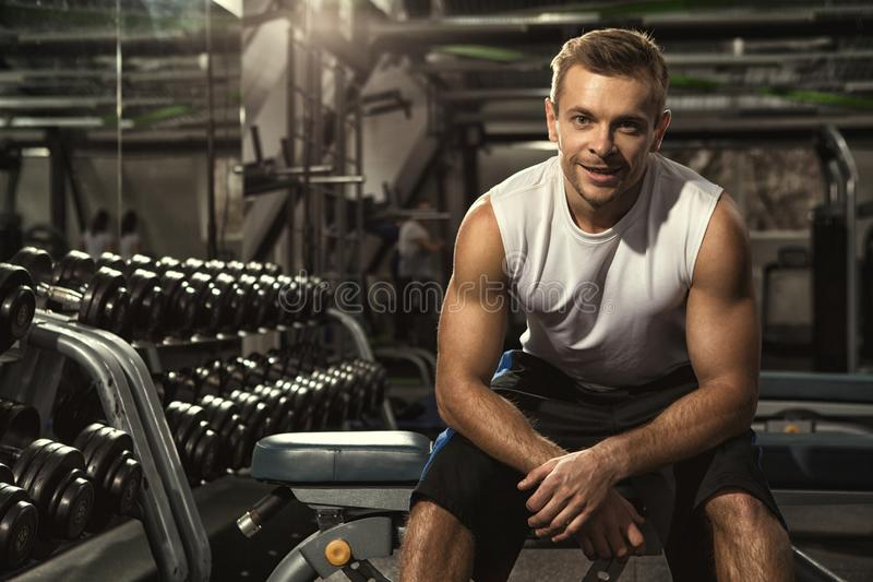 Young handsome male athlete resting at the gym after the workout stock image