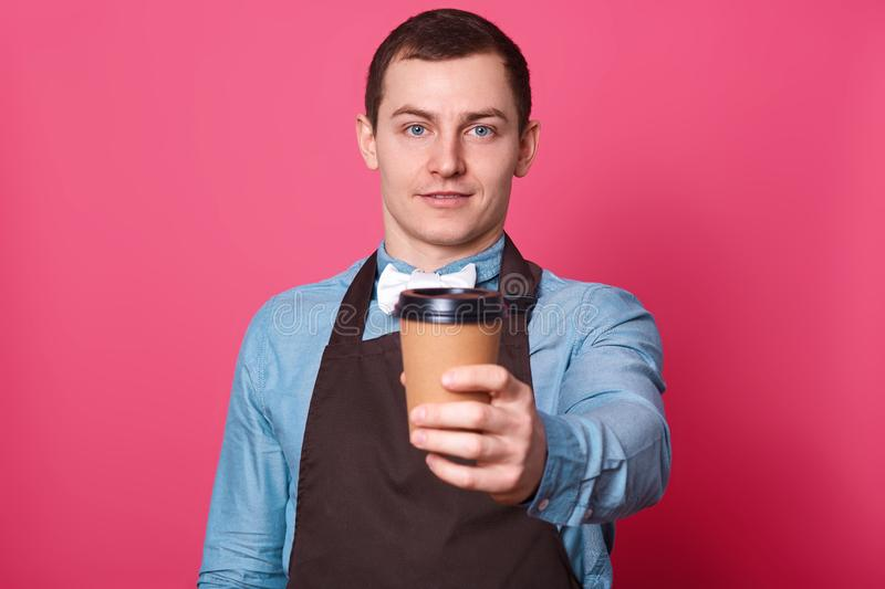 Young handsome male barista suggests you cup of coffee made by him, dressed elegant blue shirt, white bow tie and brown apron, royalty free stock photos