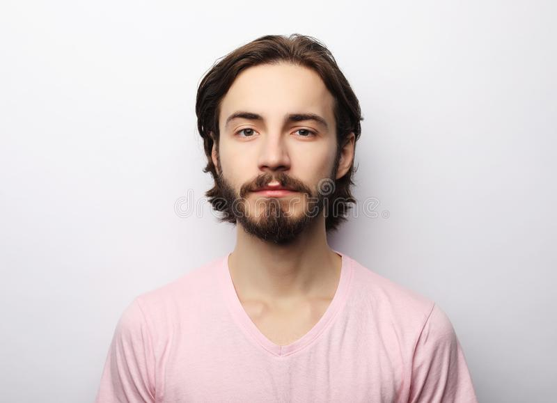 Young handsome male with beard, mustache and trendy hairdo, wears casual pink t-shirt royalty free stock photos