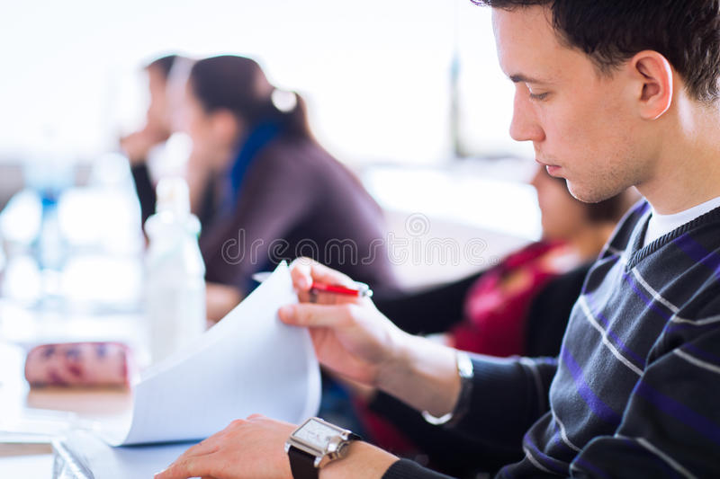 Young, handsome male college student sitting in a classroom full stock photos