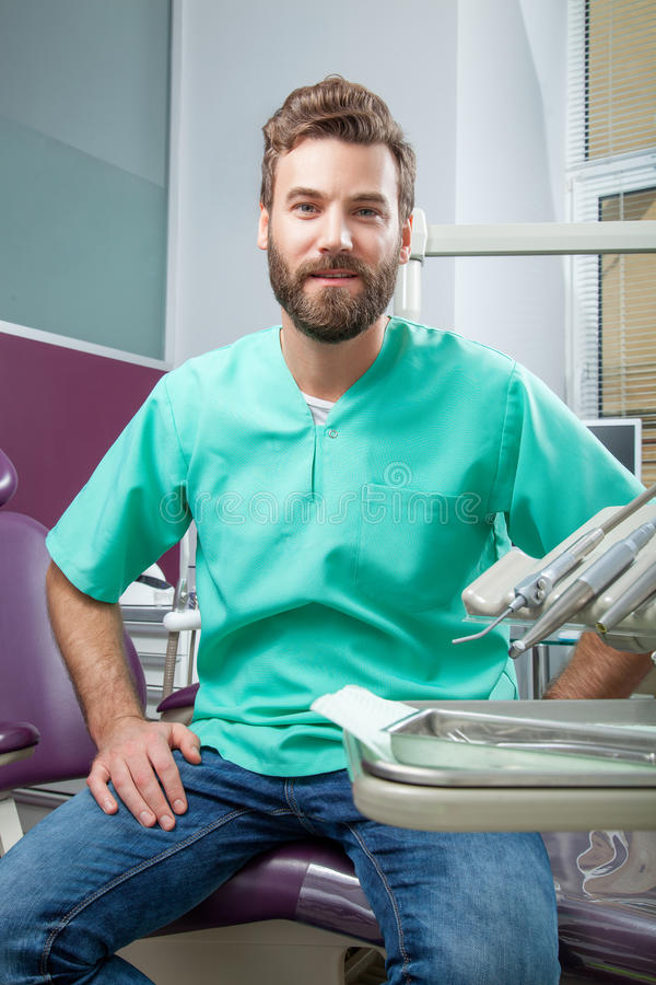 Young handsome male doctor with beard smiling with white teeth royalty free stock images