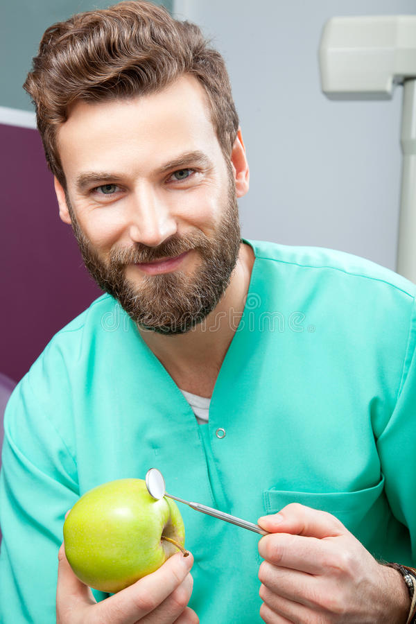 Young handsome male doctor smiling with white teeth holding apple royalty free stock photos