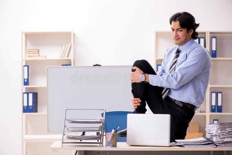 The young handsome male employee doing exercises in the office royalty free stock photography