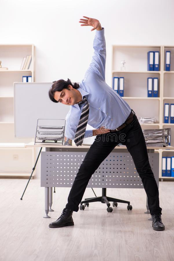 The young handsome male employee doing exercises in the office stock image