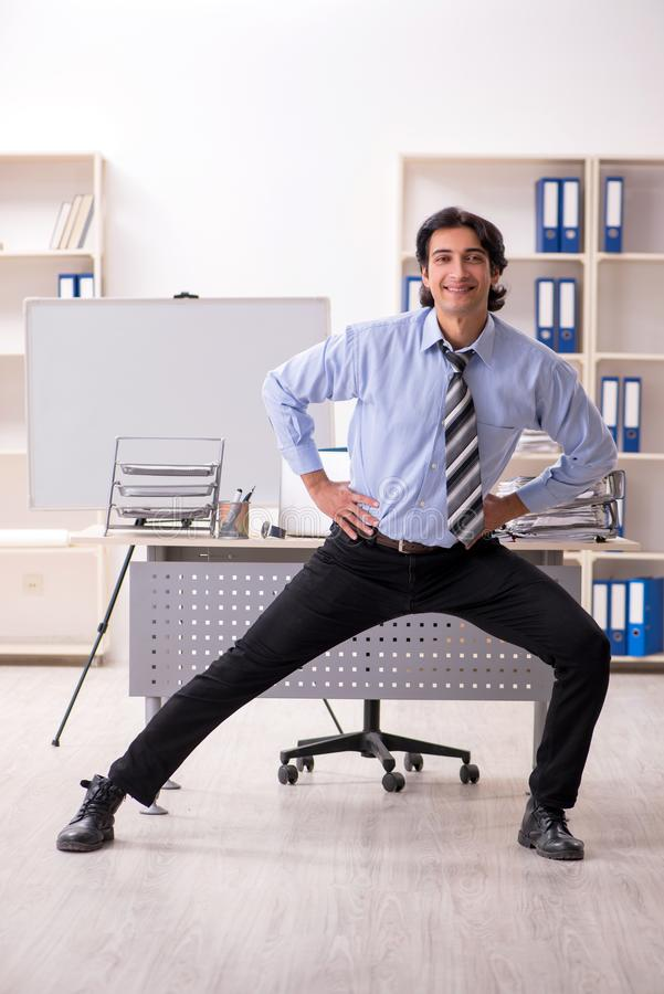 The young handsome male employee doing exercises in the office royalty free stock photo