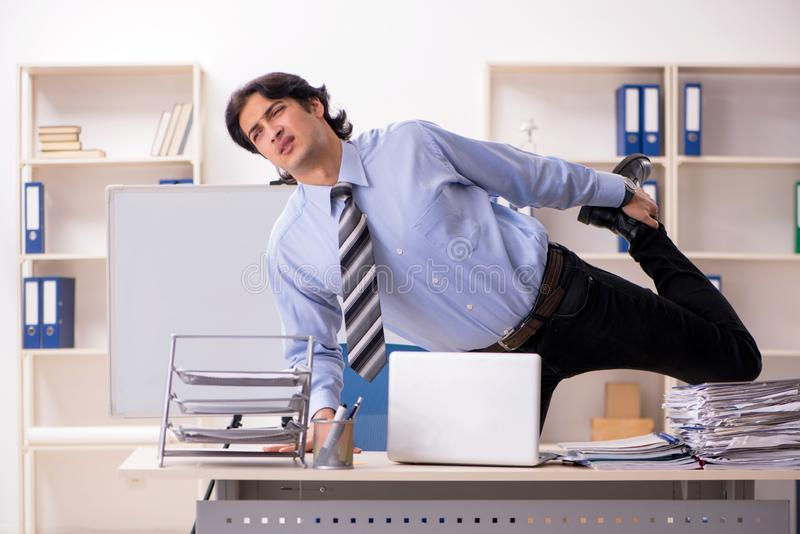 The young handsome male employee doing exercises in the office stock photography