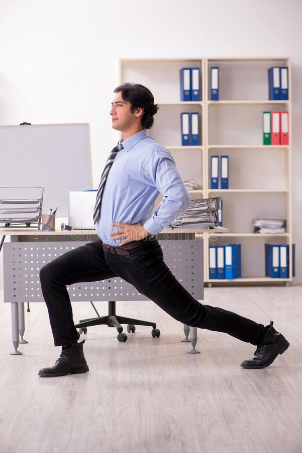 The young handsome male employee doing exercises in the office stock images