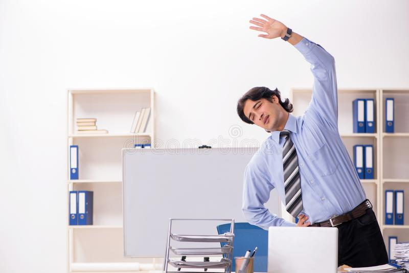 The young handsome male employee doing exercises in the office stock photos