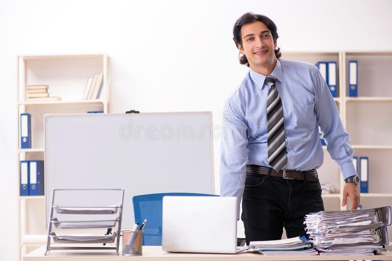 The young handsome male employee doing exercises in the office royalty free stock image
