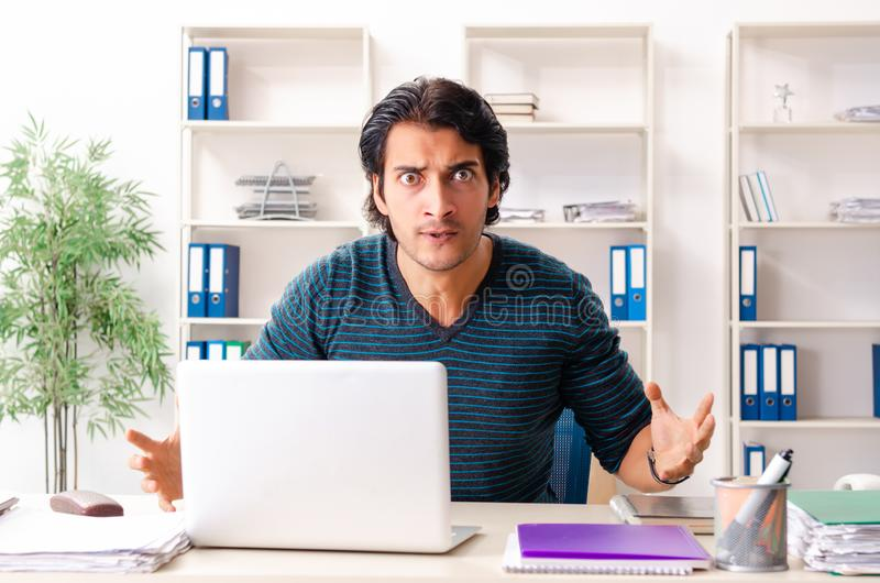 The young handsome male employee sitting at the office. Young handsome male employee sitting at the office stock photos