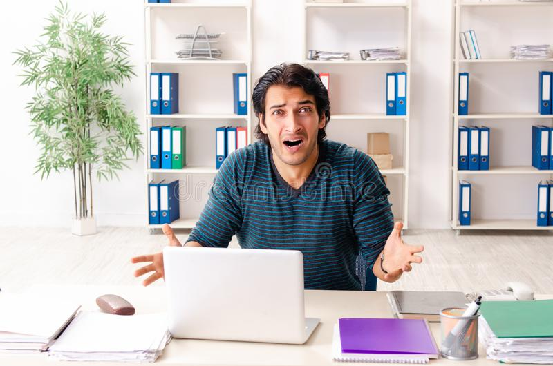 The young handsome male employee sitting at the office. Young handsome male employee sitting at the office stock image