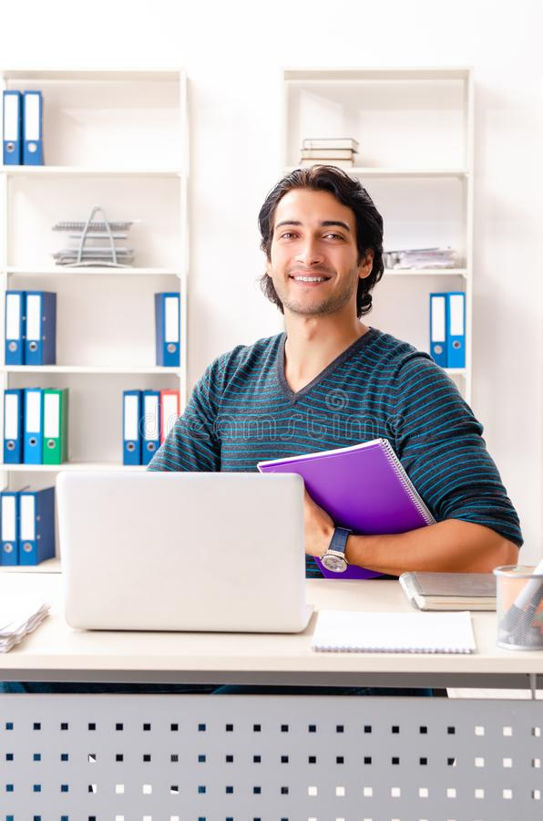 The young handsome male employee sitting at the office. Young handsome male employee sitting at the office stock photo