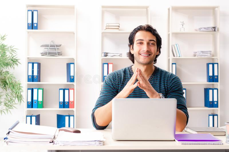 The young handsome male employee sitting at the office. Young handsome male employee sitting at the office royalty free stock photo