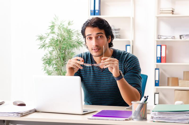 The young handsome male employee sitting at the office. Young handsome male employee sitting at the office royalty free stock images