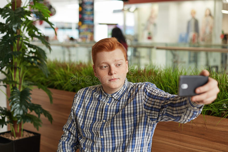 A young handsome male with red hair having natural expression while making selfie on his smartphone isolated over greenery in cafe royalty free stock image