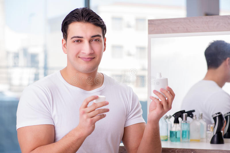The young handsome man applying face cream royalty free stock photography