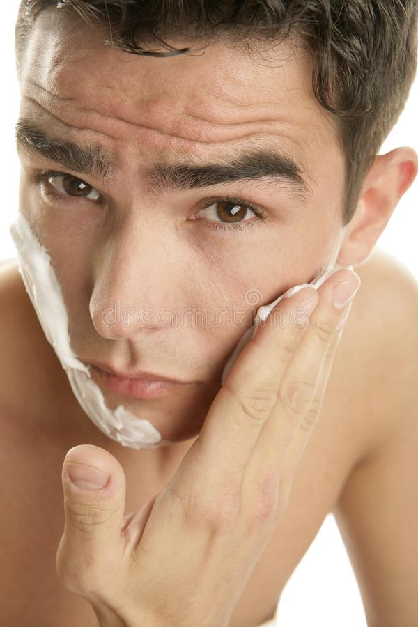 Young handsome man applying shaving foam on his face royalty free stock images