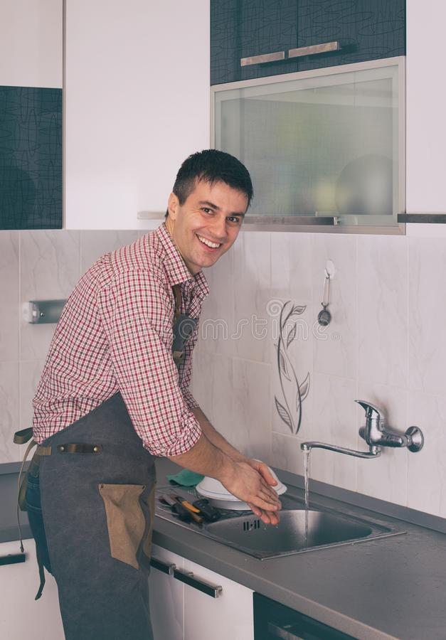 Man washing dishes in kitchen royalty free stock photography