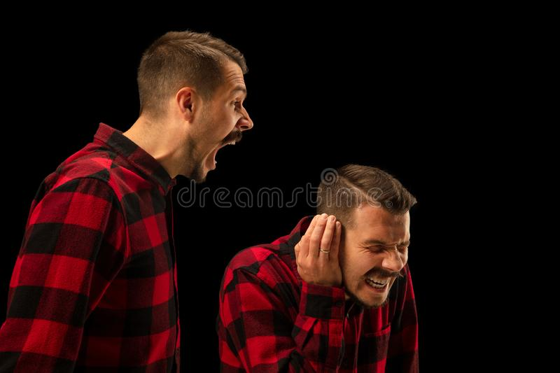 Young handsome man arguing with himself on black studio background. stock image