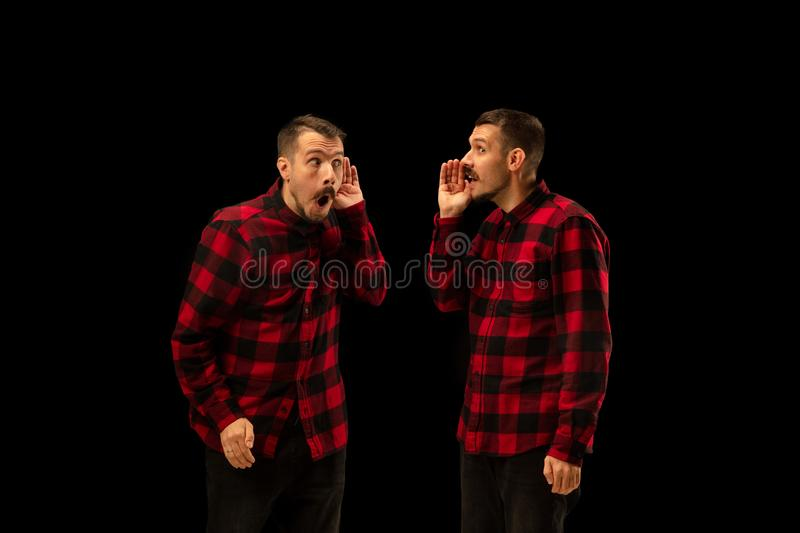 Young handsome man arguing with himself on black studio background. royalty free stock photography