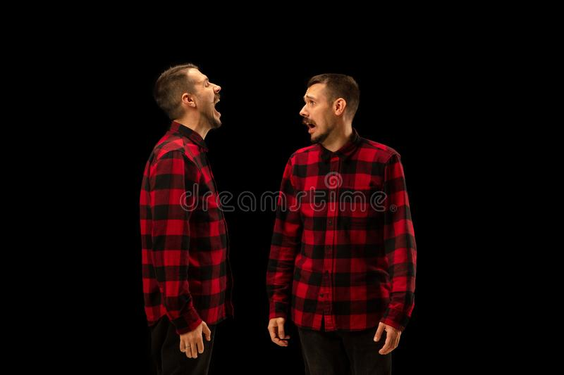 Young handsome man arguing with himself on black studio background. stock photos
