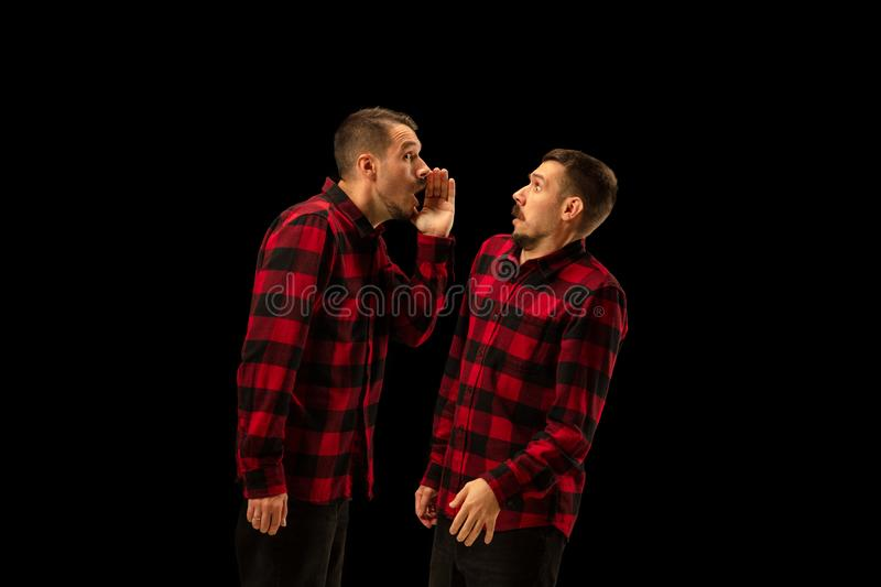 Young handsome man arguing with himself on black studio background. royalty free stock image