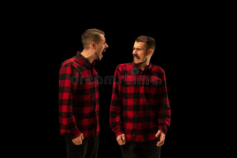 Young handsome man arguing with himself on black studio background. stock photo
