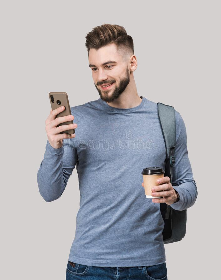Young handsome man with backpack holding smart phone and coffee isolated portrait. Smiling student or businessman studio shot stock images