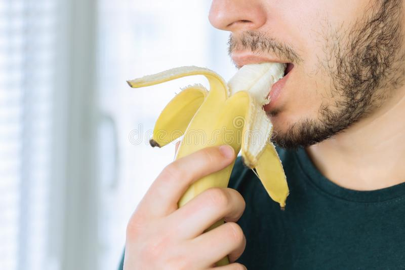 Young handsome man with a beard biting off a banana. Standing in the kitchen stock photo