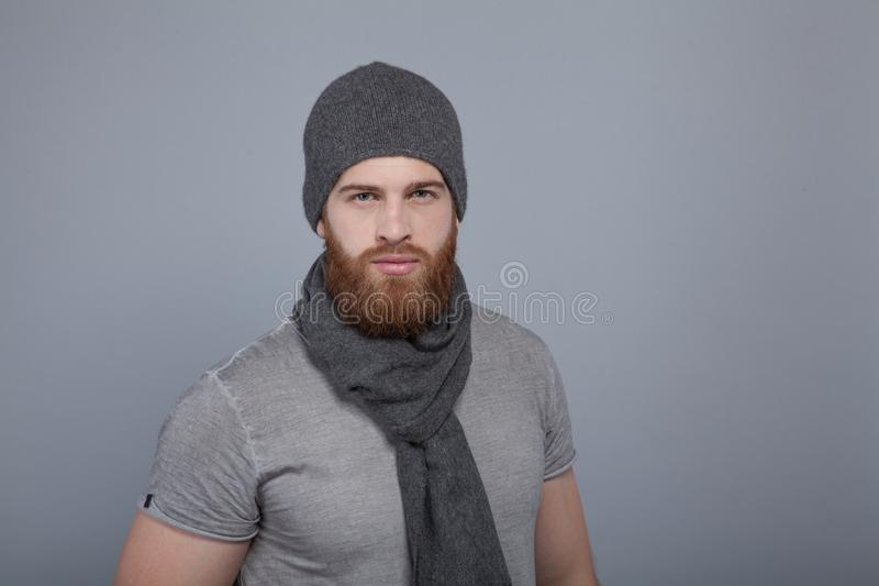 Young handsome man with the beard in grey cap and scarf standing by the grey wall and looking straight to the camera royalty free stock image