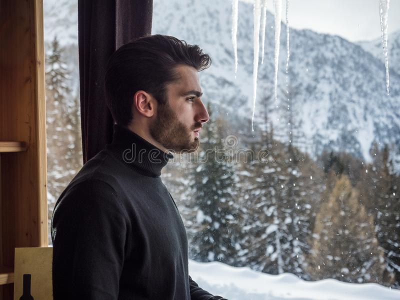 Confident man at mountains, looking at landscape. Young handsome man with beard at mountain ski resort, looking outside the window, away confidently on stock image