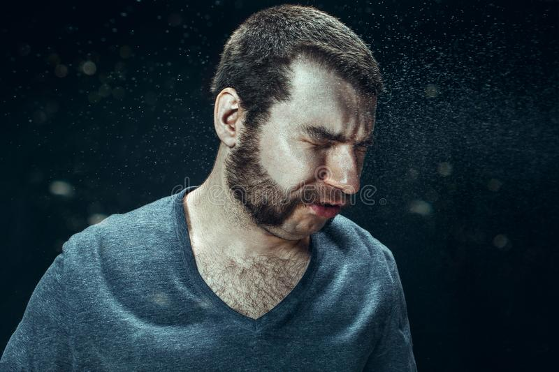 Young handsome man with beard sneezing, studio portrait stock photography