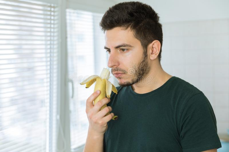 Young handsome man with a beard sniffing a banana. Standing in the kitchen stock images