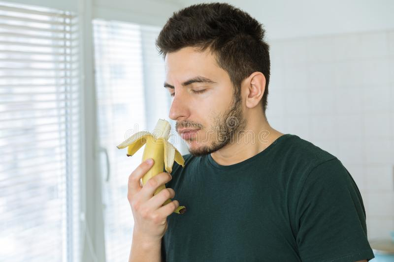 Young handsome man with a beard sniffing a banana. Standing in the kitchen royalty free stock photos
