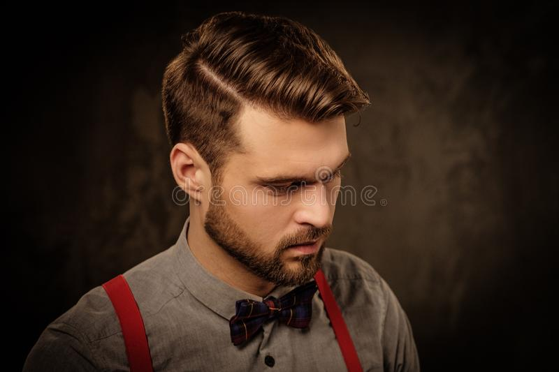 Young handsome man with beard wearing suspenders and posing on dark background. royalty free stock photos
