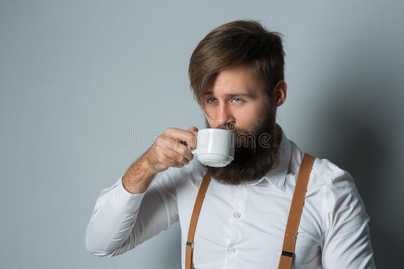 Young handsome man with a beard. In a white shirt and yellow suspenders with cup coffee or tea on a gray background royalty free stock images