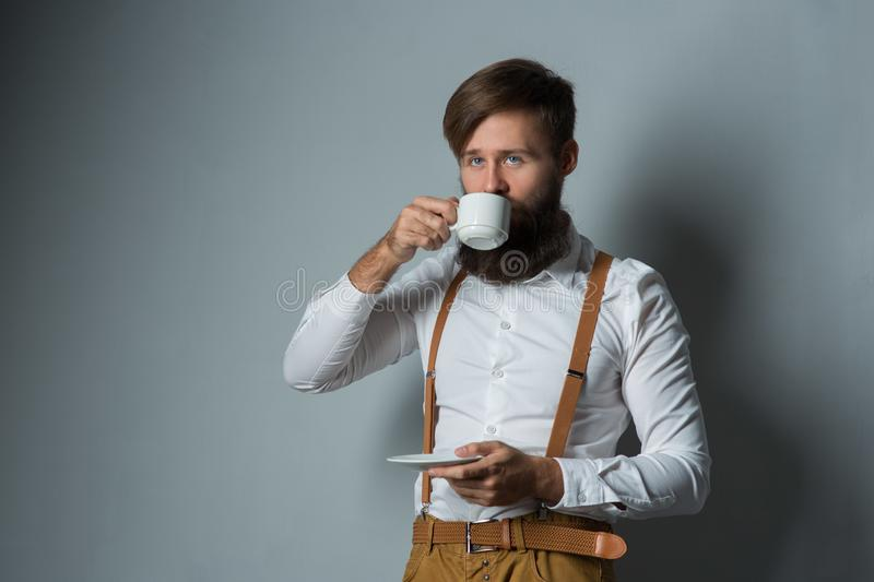 Young handsome man with a beard. In a white shirt and yellow suspenders with cup coffee or tea on a gray background royalty free stock image